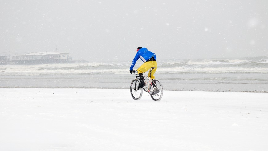 person with bike in the snow storm on the beach