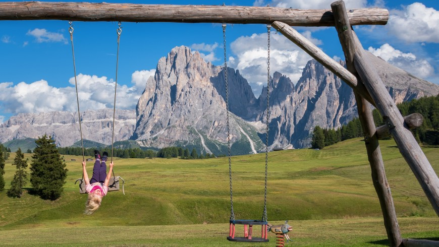 child playing in nature, surrounded by mountains