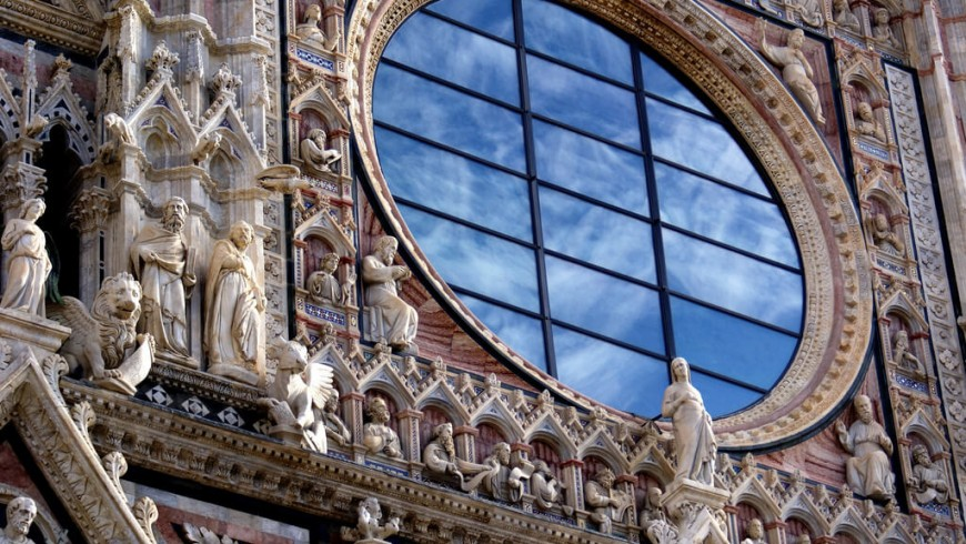 The rose window of the Duomo in Siena. The glass wall reflects the sky