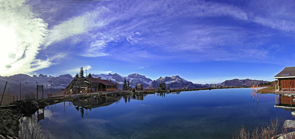 The Härzlisee lake reflects the sky (Switzerland); on the background, a mountain chain coverd with snow
