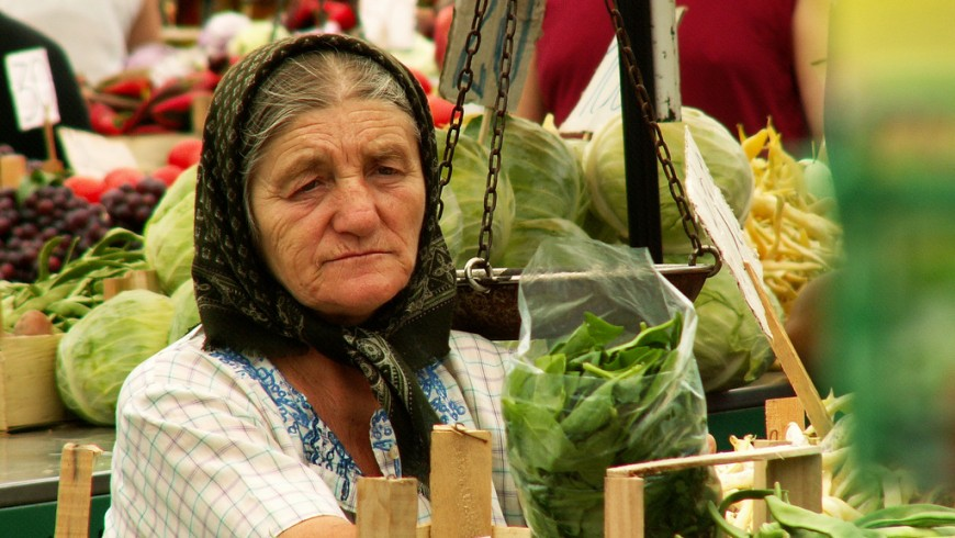 a lady at the market selling vegetables