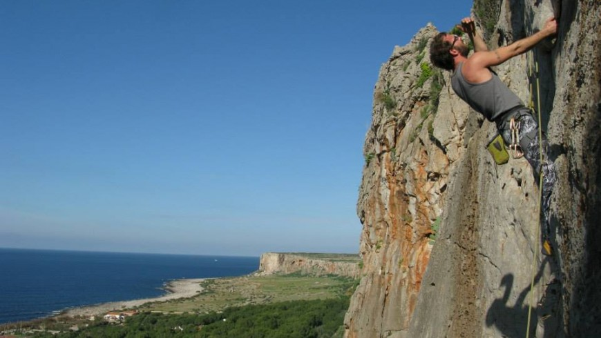 a guy climbing on the rock along the seaside