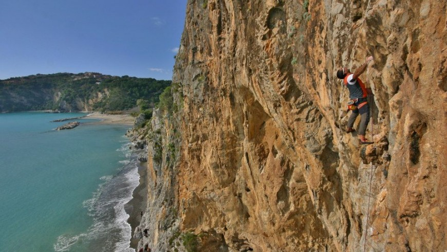 a guy climbing a red wall on the sea
