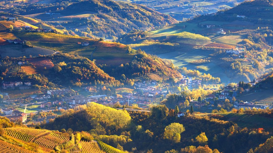 During the truffle festival, foggy morning over small town among autumnal hills and vineyards of Piedmont, Northern Italy (view from above).