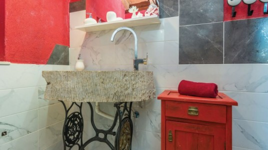 The distinctive stone sink and the restored wooden furniture, red-dyed