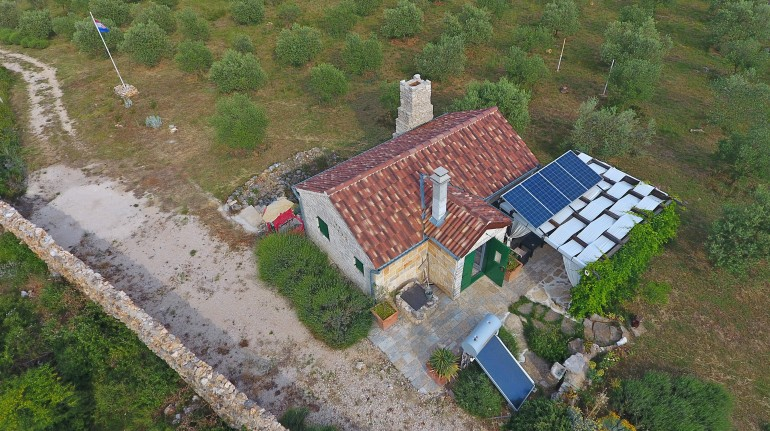 Aerial view on the house. The fluepipe, the solar panels, the water-pump, the tank, the gazebo and the olive trees are visible.