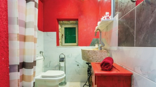 The bathroom, with red walls and white tiles