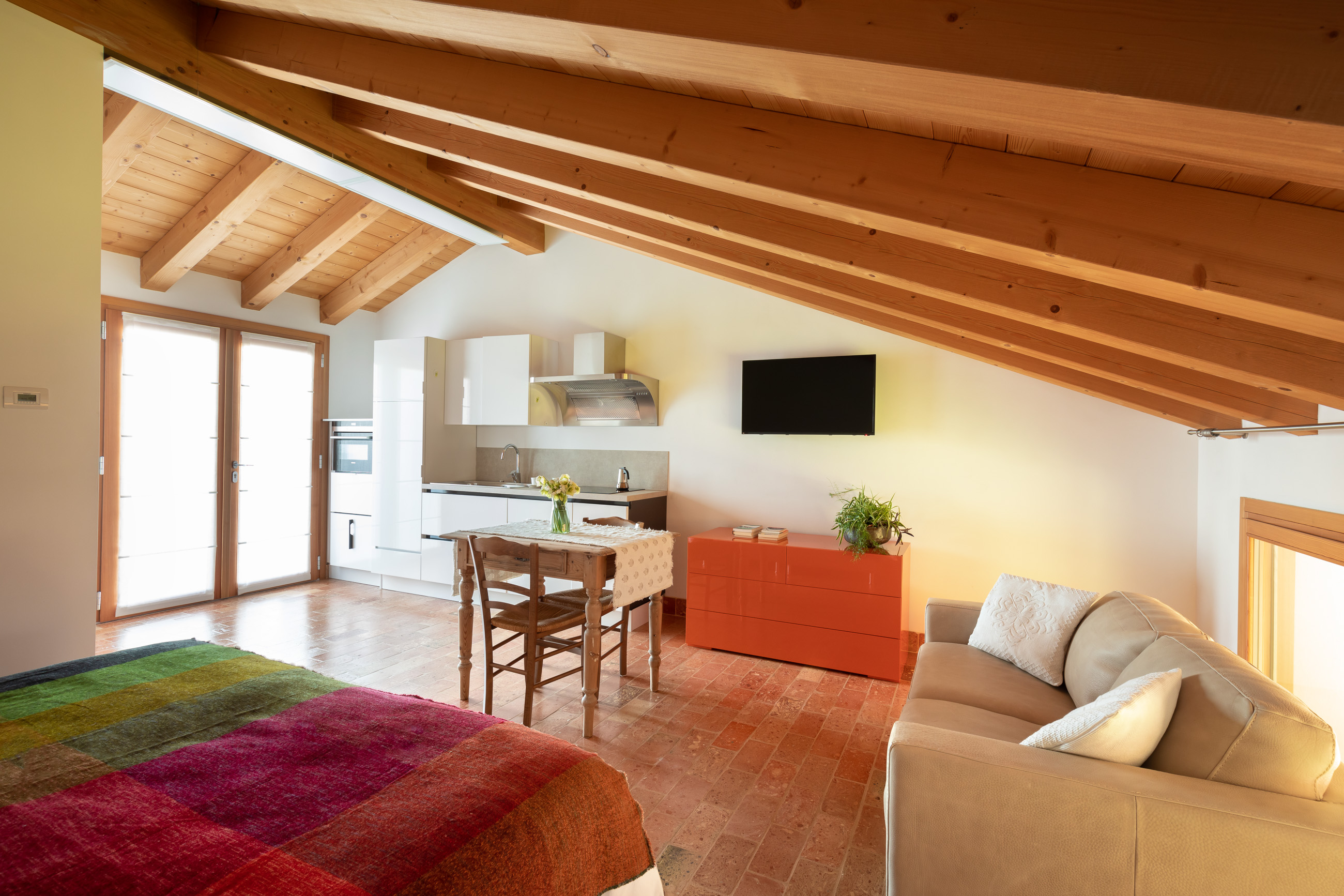 eco-friendly house Casa Fiorindo: an indoor space with modern furniture, but traditional materials (cotto tile, wood)