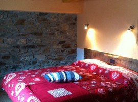 One of the rooms from the hotel, with red blankets and stone walls