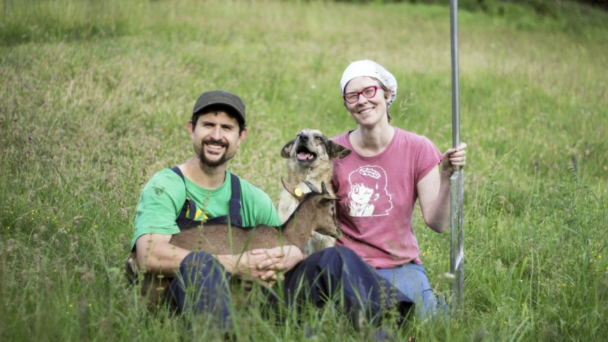 the owners of the farmhouse with one of their goats and a dog sitted in the meadow