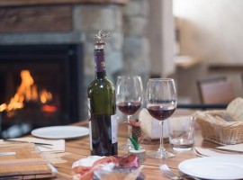 A table with a bottle of wine from the valley, ham, cheese and two glasses full of red wine