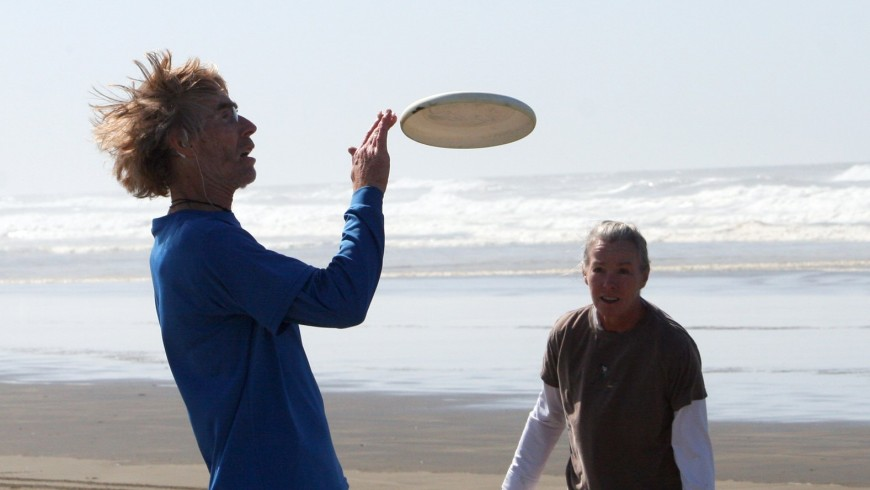Two boys playing frisbee at the beach