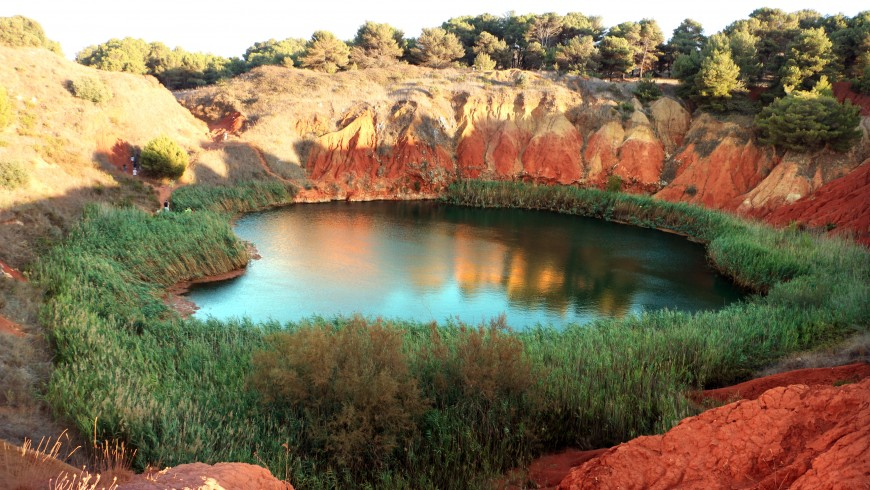 Lake of Bauxite surrounded by trees and with a green water