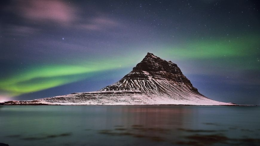 northern lights in iceland around a mountain