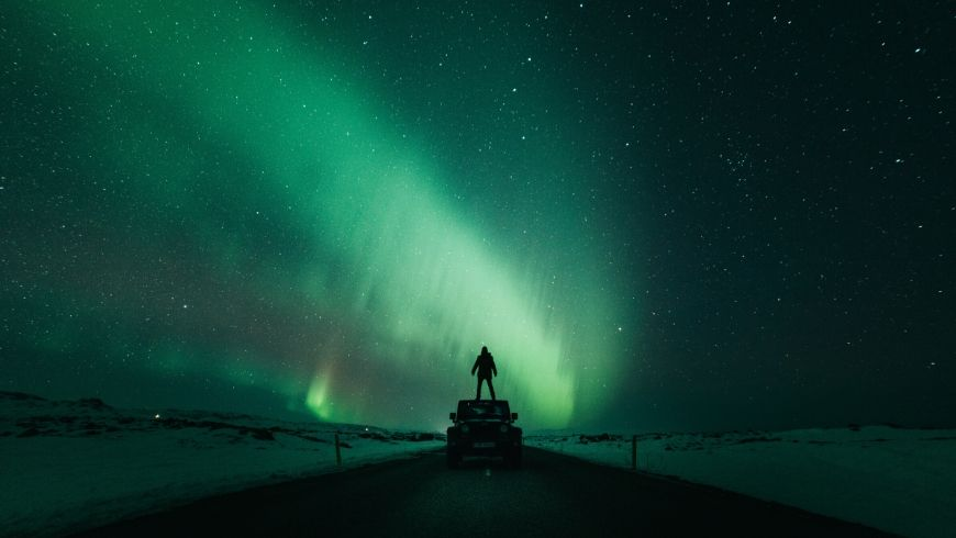 man standing in front of northern lights